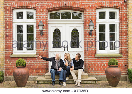 Father and mid adult couple sitting on doorstep - Stock Photo