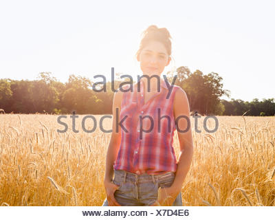 A young woman standing in a field of tall ripe corn. - Stock Photo