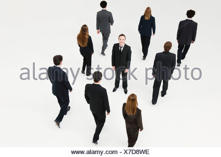 Businessman standing in midst of other anonymously dressed business professionals - Stock Photo