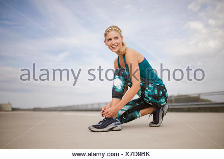 Young woman tying trainers - Stock Photo
