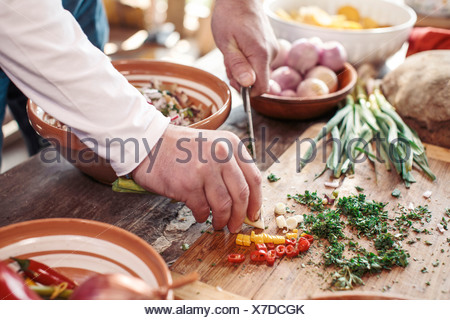 Unrecognizable person cutting bell pepper - Stock Photo