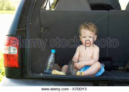 A young boy sitting in the back of an SUV - Stock Photo