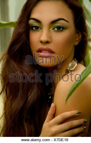 Portrait of young woman wearing green eye shadow and nail polish - Stock Photo