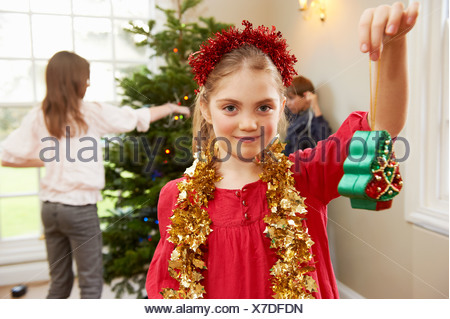 Girl playing with Christmas decorations - Stock Photo