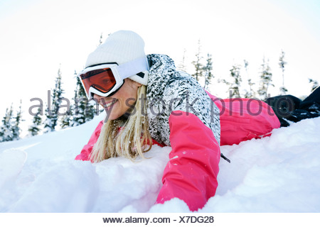 A woman with blond hair wearing ski gear lays head first in deep snow. - Stock Photo