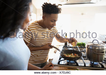 African American mother and teenage son cooking at stove in kitchen - Stock Photo
