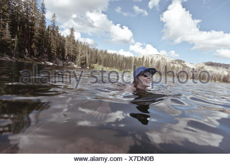 woman swimming in mountain lake, Wyoming, America, USA - Stock Photo