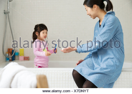 Mother with female toddler standing in bath with tooth brush - Stock Photo