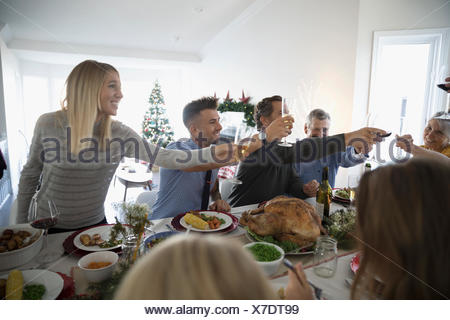 Family and friends toasting champagne glasses at turkey Christmas dinner table - Stock Photo