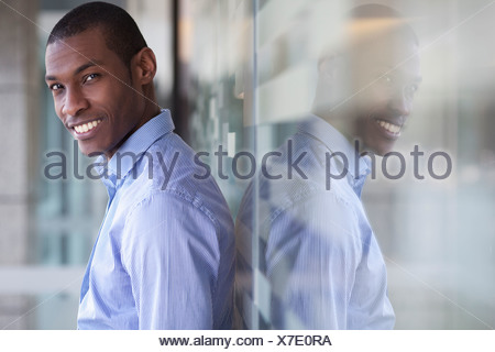 Portrait of businessman leaning against wall - Stock Photo