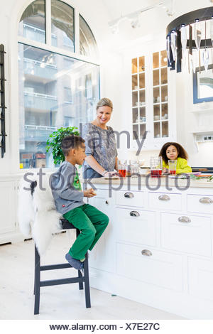 Happy mother with children having breakfast at kitchen island - Stock Photo