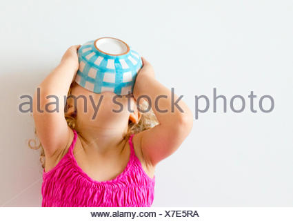 Girl with head back holding cereal bowl to her mouth - Stock Photo