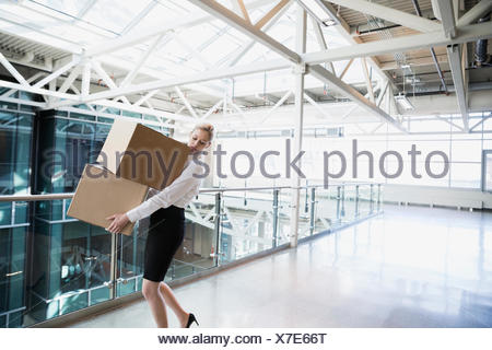 Businesswoman carrying cardboard boxes in atrium - Stock Photo
