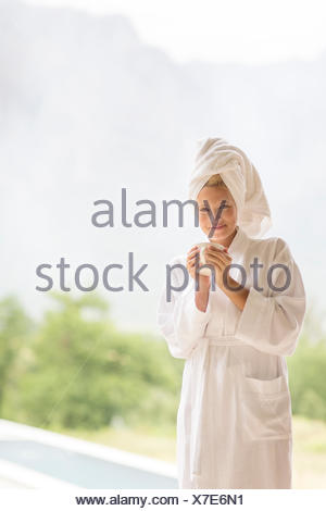 Woman in bathrobe having coffee outdoors - Stock Photo