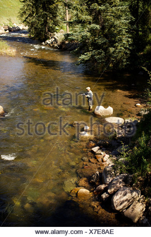 A fisherman adjusts his fly rod before fishing. - Stock Photo