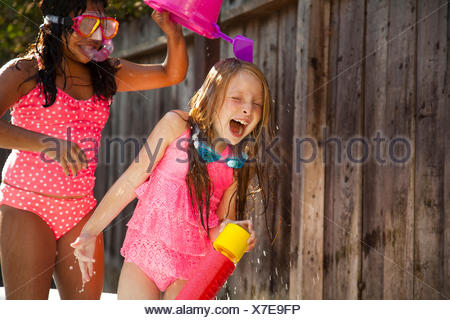 Two girls chasing each other with water in garden - Stock Photo