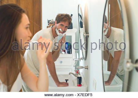 Woman brushing teeth, husband shaving - Stock Photo