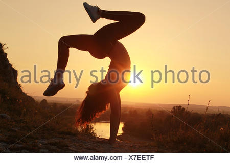 Young woman doing handstand at sunset - Stock Photo