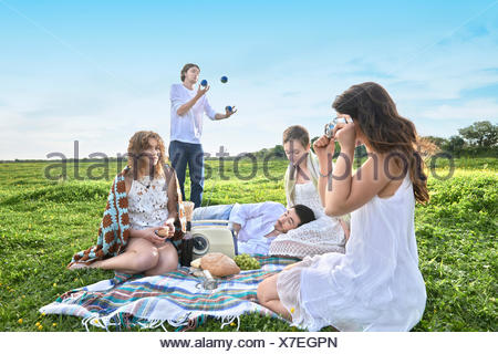 Group of young adult friends having a picnic in field - Stock Photo