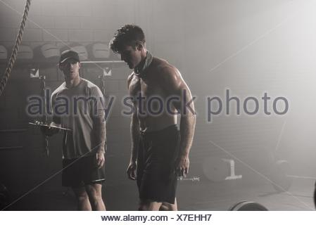 Bare chested, mid adult man, standing with trainer in gym - Stock Photo