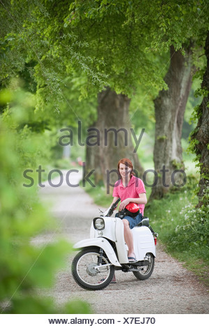 Germany, Bavaria, Young man on moped, smiling, portrait - Stock Photo