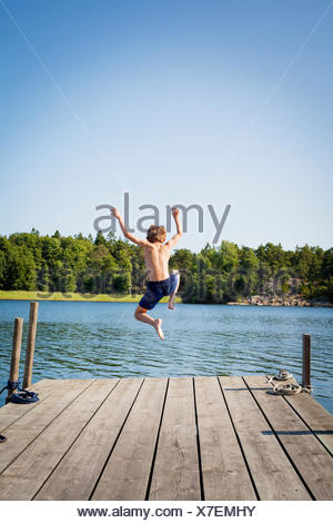 Sweden, Uppland, Runmaro, Barrskar, Rear view of boy (6-7) diving into water from jetty - Stock Photo