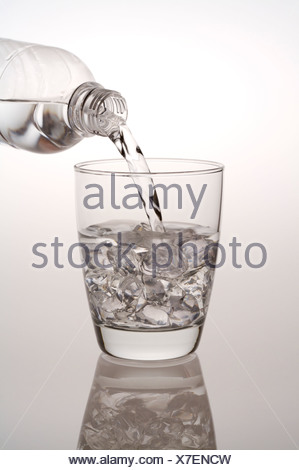 Water being poured from a water bottle into a glass filled with ice cubes - Stock Photo