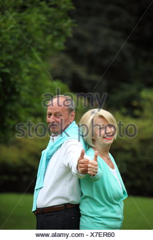 Enthusiastic senior couple giving a thumbs up - Stock Photo
