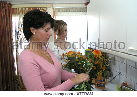 Grown up mother receiving flower on mothering day from grown up daughter in law - Stock Photo
