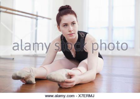 Teenage ballerina sitting on floor in ballet position at ballet school - Stock Photo