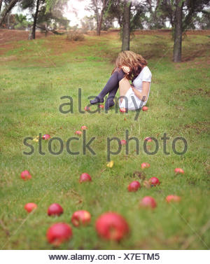 Woman sitting on grass in an apple orchard - Stock Photo