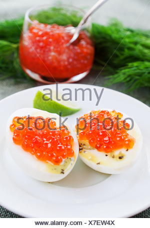 Eggs and caviar on white dish - Stock Photo
