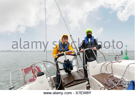 Two sailors standing at the stern of a yacht - Stock Photo