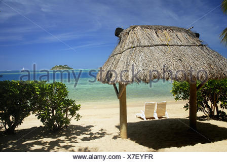 Fiji, Mamanuca Islands, Malolo Island, Beach With Two Beachchairs Under Grass Hut Beach Hut,/Nwadingi Island In Distance. - Stock Photo