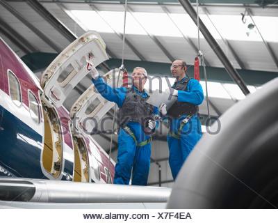 Workers examining airplane in hangar - Stock Photo