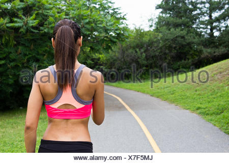 Young woman running on the jogging trail - Stock Photo