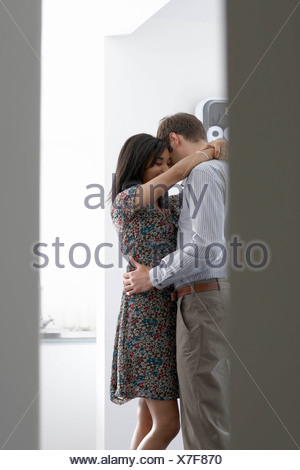 Man and woman cuddling in office - Stock Photo