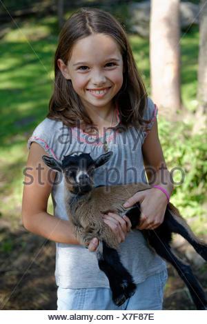 Girl holding a dwarf goat in the petting zoo at Schopperalm, Schopper Alm, Gießenbachklamm gorge near Kiefersfelden, Inn Valley - Stock Photo