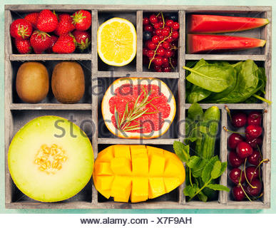 Vegetables and fruits in wooden box for vegan, gluten free, allergy-friendly, clean eating and raw diet. Blue background and top view - Stock Photo