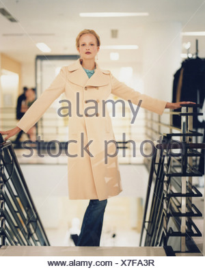 Female blonde hair off face wearing drop earrings, blue top bow at neck under cream double breasted coat and jeans standing at - Stock Photo