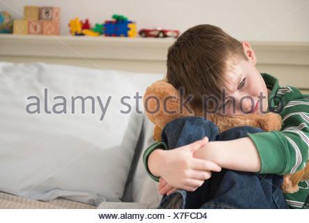 Portrait of sad boy (4-5) snuggling teddy bear - Stock Photo