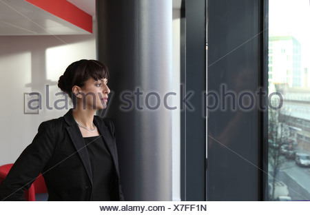 Businesswoman looking out office window - Stock Photo