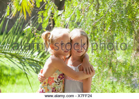 Candid portrait of two girls with arms around each other in garden - Stock Photo
