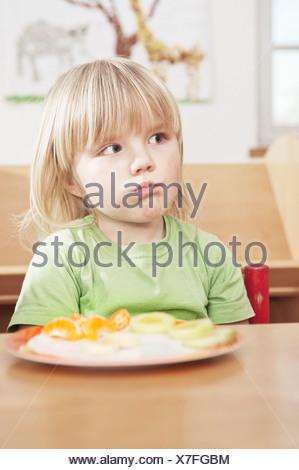 Little Girl Sitting At Table, Kottgeisering, Bavaria, Germany, Europe - Stock Photo