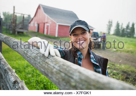 Portrait of smiling rancher leaning on fence post - Stock Photo