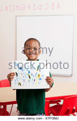 Boy holding picture that he has drawn in school - Stock Photo
