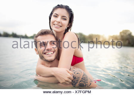 Attractive young couple hugging in lake - Stock Photo