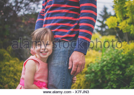 Close-up of a Smiling girl hugging father's leg - Stock Photo