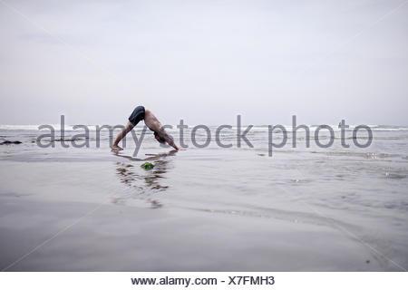 Man doing downward dog yoga pose on beach - Stock Photo