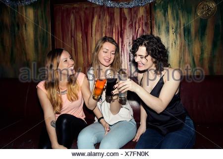 Three adult female friends raising a glass in bar - Stock Photo